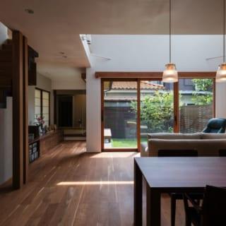 """1階リビング~ダイニング~和室/キッチンからは、中庭はもちろん、奥の和室も望める。和室はぬくもりのある土壁。ちょっとした""""離れ""""のような使い方や、来客用としても重宝するのだとか"""
