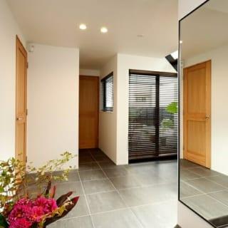 玄関ホール。正面に中庭、右手に鏡を配するなど、空間をより広く感じさせる工夫が見られる。