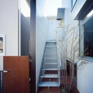 黒い壁と白い壁の間に設けた坪庭は二世帯で共有。室内空間を最大限に取るため、階段は外階段に。地域コミュニティに根付いた暮らしをしている親世帯のライフスタイルを考慮し、1階玄関横の開口部のみ一般的な目線の高さに窓を設けて街行く人とつながるようにしている。