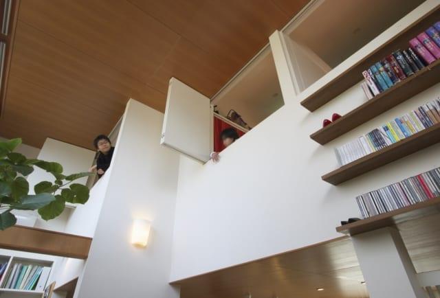 2階の子ども部屋から顔を出す子どもたち。吹き抜け部分を介して、2階同士や1階の人と会話ができる