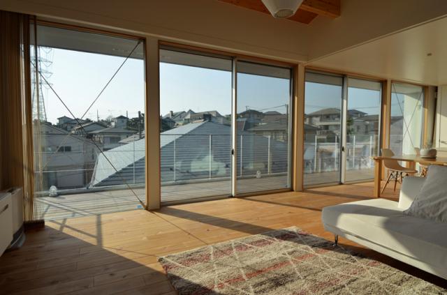 2階 リビングダイニング/大きな窓で西の間口が大胆に開かれている。ベランダと隣家の屋根は同じ高さにそろえられ、眺望を守るだけでなく隣人とお互いの目線が気にならないよう配慮されている