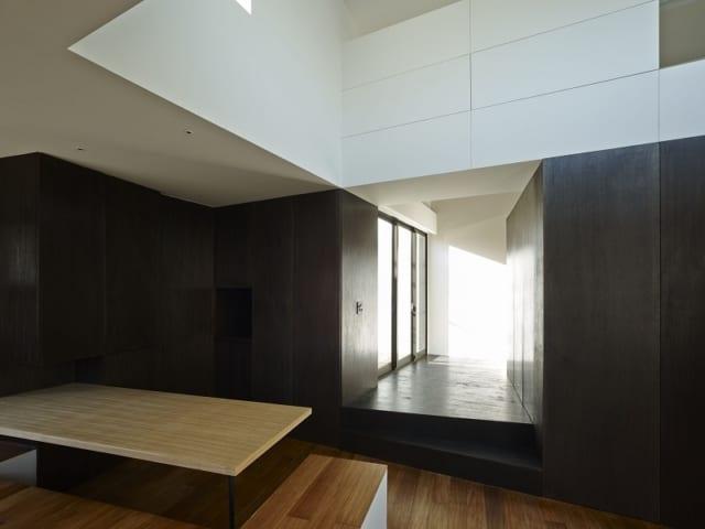 2階 リビング/写真左手の引き戸を開けるとキッチンがある。扉を引き戸にすることで、リビングの全体的な印象がすっきりとシンプルなものになった。はっきりとした色のコントラストもモダンなイメージを与える。写真中央の通路突き当り右に納戸と寝室への階段があり、人が集まるスペースと絶妙な距離感を保っている