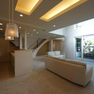 白を基調とした明るい室内。吹き抜けや間接照明、階段に用いられたロートアイアンなどにより、空間にさまざまな表情をつくり出している。