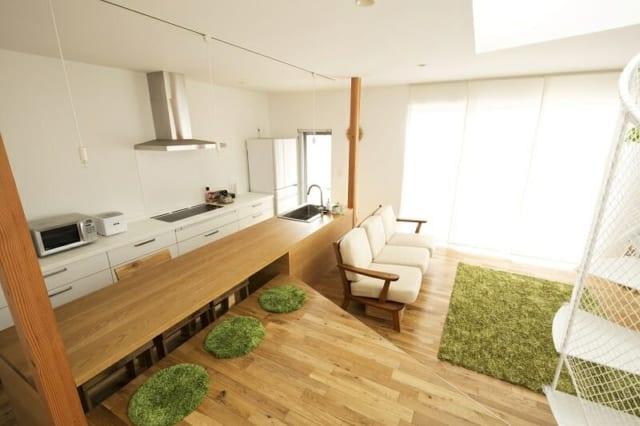 1階リビング~ダイニング~キッチン/一部が吹き抜けとなったLDKは明るく開放的。キッチン部分と一体となっているダイニングテーブルの手前側は、床の段差を使って掘りごたつのように座ることができる