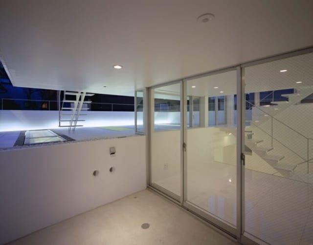 1Fの左手は駐車場、奥はベッドルームを半分地下に埋め込んだテラス、ガラス戸を開けるとマルチファンクションルームにダイレクトにアクセスすることが可能。こちらは将来親と一緒に住む際に親のお部屋になるほか、客間や趣味の部屋としても活用することができるように設計された。