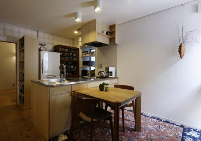 1階の親世帯のキッチンとダイニング。元の家の使い勝手をベースに、何でも手を伸ばせばすぐ届くようにコンパクトに仕上げている。上部の欄間は開閉式の障子。明かりがさりげなく伝わり、空間に奥行きを持たせている