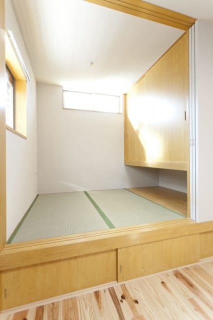 1階畳コーナー/畳の下は収納になっている。以前は西に位置する奥の壁に大きな窓があったが、暑い西日を遮って明るさだけを得られるよう、ハイサイドの窓に変更した。対角の東側にもハイサイドの窓があり、風通しは極めて良好
