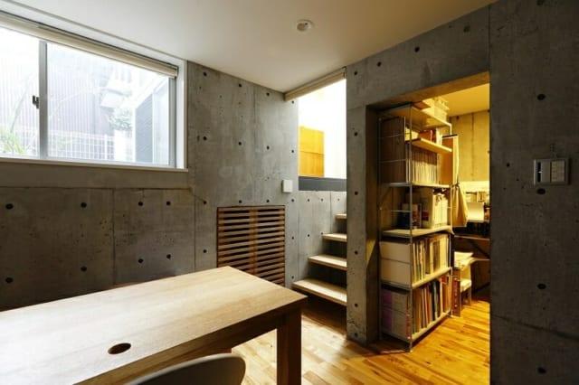 地階 ワークスペース入口/写真中央の階段の先が玄関ホール。地階は、階段で玄関ホールから半階分ほど下がった高さに位置する。写真左の窓から見える『タテノニワ』を通して自然光が入り、穏やかな明るさ。写真右奥は書庫兼ウォークインクロゼットとして使用中だが、広いので寝室や書斎としても使える