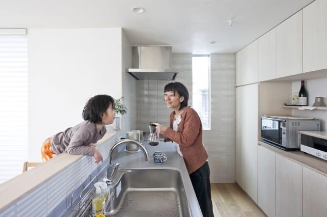 対面式のキッチン。リビングで遊ぶ子どもと楽しく会話しながら料理ができる。横には洗濯機置場もあり、洗濯物はここからすぐにベランダに干すことができる