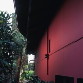 """外観・裏手/垣根に面した裏手の外壁は板張りとせず、ベンガラ色の塗料を吹き付けたボードを用いている。北園さんいわく、「裏手なんですけど""""裏""""に見えないよう、落ち着いていて、かつ鮮やかさもある色を選びました」。この外壁は、Hさんの奥さまもいたくお気に入りだそう"""