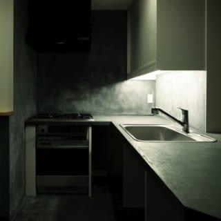 キッチン3/キッチン部分はモルタル仕上げの土間となっており、リビングダイニングより14センチ程度低くなっている。シンク下部にはあえて収納を設けなかった。必要に応じて移動式のワゴンやラックなどを入れて使うことで、自由な収納スペース確保が可能に