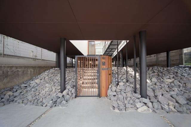 黒で統一した配管や構造の丸い柱が並ぶ不思議な空間。その中央には、ここからは家だと主張するように門扉が立っている