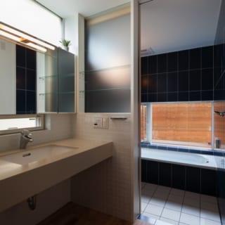 洗面所~浴室/水回りは広めに、というFさんご夫妻からの要望を受けて設計。鏡の上下に窓を配し、すっきりとした白でまとめられた洗面所と、落ち着いた紺色のタイルが手入れしやすそうな浴室のコントラストが美しい