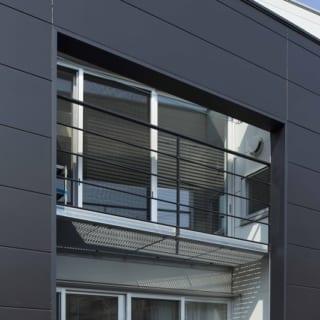 1階と2階の中間に設けた黒い壁の開口部。目線のレベルでは視線を遮りつつ、上部の空、下部の緑を見ることができる。隙間から見る景色が奥行きをつくりだす。