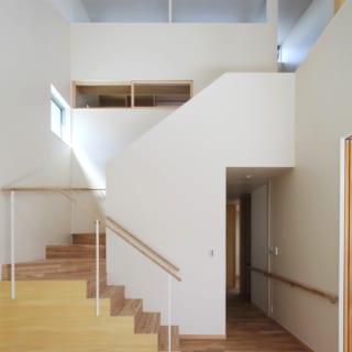リビング~階段/階段は吹抜けのリビング内。外からの視線が気にならない階段の踊り場や高い位置にも窓を配し、ふんだんに採光。階段途中の2階の木枠部分は、書斎から1階を見渡せる室内窓