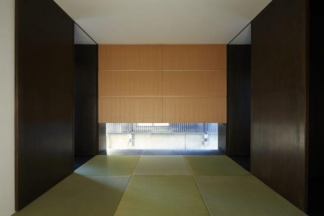 1階 和室/写真正面のタモ材を使用した大きな造り付け収納の明るい色合いを、壁面のダークブラウンが引き締め洗練された印象。縁のない琉球畳を選び、よりオリエンタルな雰囲気になっている。 窓越しには公園のフェンスで圧迫感があるため、窓は低く配置した