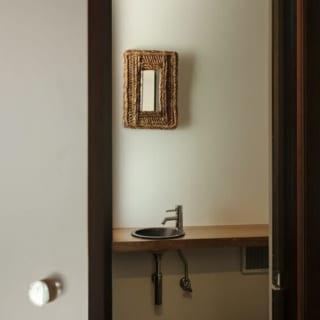 1階に新設したトイレ。手洗いカウンターには栗の一枚板を使用。アクリル製の取っ手はトイレ内の照明を廊下にさり気なく伝える役割も。扉を閉めると壁の面材と一体化し、一見するとトイレがあるとはわからないようになっている。