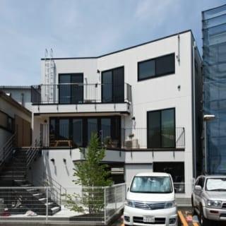 前面道路から見る住居部分とは対照的な、南側に開いた開放的な住居。プライベートな外階段を上がると広いテラスが広がり、そこを通って玄関に入る。