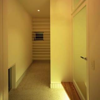 玄関/リビング扉上部は風を通す換気窓。床は白モルタル洗い出し。玄関収納には、スキー板などの長いものやベビーカーなどを置けるスペースを確保した。