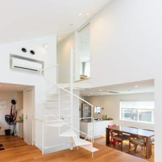 K邸のリビング。写真右奥がダイニング、左奥が書斎スペース、中央のらせん階段を上がると3階。高さ制限のため、屋根が勾配になっている