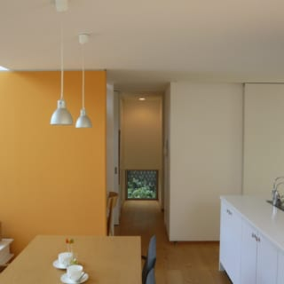 元気なオレンジ色の壁がLDKのアクセントに。水回りに向かう動線の先にも開口部が設けられ緑が楽しめる