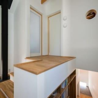 本棚のある階段室。小さな丸窓が空いているところが娘さんの個室。音楽のほか、ヨットにも乗るという娘さん。個室には船舶用の丸窓とランプをつけた