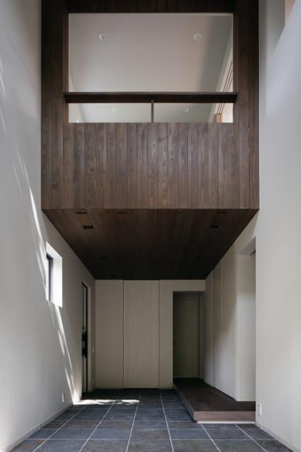 1階 土間から和室を見上げる/吹抜けの一部には2階の和室が張り出している。ここはオイル塗装した杉板張り。空中に木箱が浮いているアートのような空間だ。和室の吹抜け側は断熱性のある和紙ブラインドで、写真は全開した状態。適度な開口を設けたおかげでピアノの音響もいい
