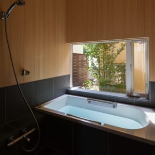 1階浴室/御影石とヒバ材が、落ち着いた日本旅館の内風呂のような印象を与える浴室。窓からはヤマボウシが見え、秋に美しく色づいた葉を眺めるのも楽しみ