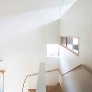 階段上部/踊り場の上部には明かりとりの小さな窓を設置。この窓があるだけでも採光が全然違う。写真右の横長の窓は2階の書斎の室内窓。この窓の正面にリビングの南向きの大きな窓があり、書斎から外の景色も見える