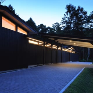 外観 塀ライトアップ/日が落ちると、板塀に温かみのある明かりがともる。鬱蒼と茂る深緑の中に黒い板塀が浮かび上がり、老舗旅館のような高級感を醸す