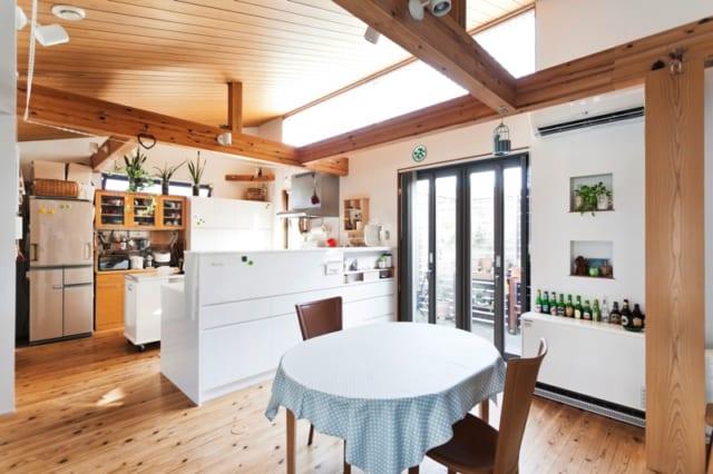 2階 ダイニング・キッチン/床は節のあるスギ、天井は無節のスギを用いることで、天然木の風合いがありながらすっきりとした印象に。キッチンはダイニングとリビングを見渡せるレイアウトで、どこにいても気軽にコミュニケーションがとれる。キッチンカウンターの下部はキッチン側もリビング側も収納を設けている