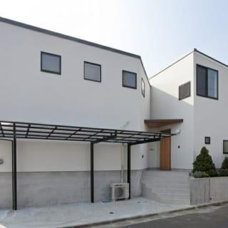 外観~北から/家の切り替わりの間に玄関ポーチを設け、『包み込む』感じを演出。シダー材のポーチ天井と、ピーラー材の扉が白い壁に温かみのあるアクセントを加えている。住宅街からの目線を遮るとともに風が抜けるよう北側の窓は高い位置に配置