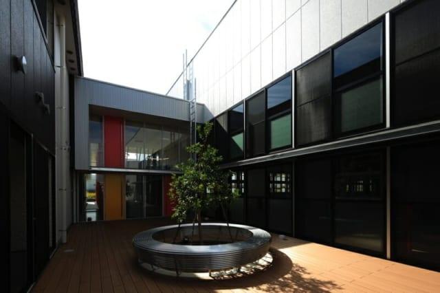 撮影:GEN INOUE  中庭/適度な空間を取り入れ、窓を多く設置。グリーンを囲むベンチやウッドデッキをしつらえ、社員が憩える心地よい空間に仕上がっている
