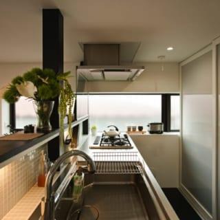 「オールステンレスの業務用っぽいキッチンにしたかった」と奥様。コンロ奥には幅27cmの出窓を設置し、西側にもかかわらず十分な明るさを確保。後ろは食器などをしまう収納棚