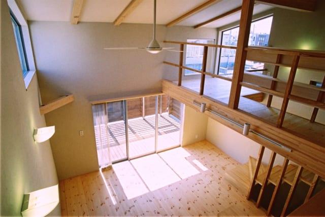 2階 リビング/ダイニング、リビングは天井高3.6~5mの吹抜けで、明るく開放感たっぷり。その先にはテラスが広がる。床はパインの無垢材、塗り壁は調湿、消臭にすぐれた自然素材のシラス壁。この塗り壁は1階の寝室でも使用。寝室はSさん夫妻の手で壁塗りした(竣工時撮影)