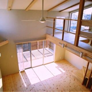 2階 リビング/ダイニング、リビングは天井高3.6~5mの吹抜けで、明るく開放感たっぷり。その先にはテラスが広がる。床はパインの無垢材、塗り壁は調湿、消臭にすぐれた自然素材のシラス壁。この塗り壁は1階の寝室でも使用。寝室はSさん夫妻の手で壁塗りした