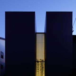 【写真】正面から見た、夜のT様邸。ガラス部分からもれるオレンジ色の光が、前の道を照らす