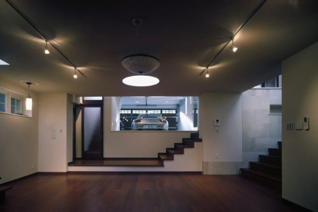 半地下リビング/贅沢な広さを確保したリビングからはインナーガレージの愛車を眺められる。写真右奥は、玄関から直接リビングに降りられる階段。写真右手前の幅の広い階段は、1階のキッチン・ダイニングスペースに続く。写真左のガラス扉を開けると2階の主寝室につながる階段もある