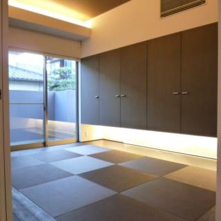 天井や壁にあえて濃色を使い、落ち着きの空間に仕上げた和室。市松敷きの畳と光の演出でモダンな雰囲気に。