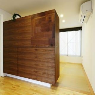 1階 和室/フローリングスペースにある造り付けの収納棚の先は畳の和室。現在は寝室として使用している。写真奥の窓は隣家の窓とずらして設置。また、1階といっても敷地の高さより半階ほど高いので視線の位置も異なり、プライバシー面も安心