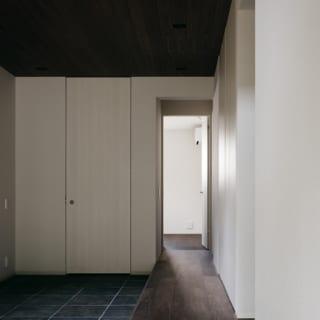 1階 土間を上がった廊下/廊下から写真右へ入ると2階への階段があり、写真奥へ進むと2つの子ども部屋と主寝室。廊下は2階のLDKや和室などのパブリック空間と、主寝室などのプライベート空間を分ける境界線の役割も果たしている