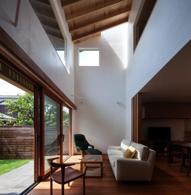1階リビング/建具も天然木を使用しているY邸。高い天井が印象的なリビングは、真っ白な漆喰の壁に合わせ、天井はあえてスギの構造材を見せることで無機質さを抑えて木質感を出し、視線を留めて楽しめるポイントをつくった。床材は、赤みを帯びた色合いが美しいアメリカンブラックチェリーを使用