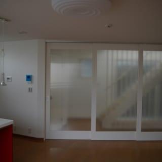 2階LDK 引き戸/LDKの出入口は開放感のある大きな引き戸。素材は半透明のポリカーボネート。引き戸は2階~3階への階段に面しているため、3階の個室へ行き来する家族の気配がわかりやすい