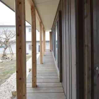 デッキの廊下/リビング棟と寝室棟に行き来するときは、一度外に出て、屋根付きのデッキを渡る。これも生活に変化を付けるユニークなアイディアだ