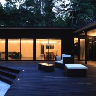 外観 バルコニーライトアップ/塀の上辺に沿って見えないように設置された照明が渡り廊下の屋根と床をほんのり照らし、贅沢な非日常感を演出。デッキ・テラスはリビングに向けて広げ、屋内と屋外の一体感を高めている。また、縁部分にもライトを仕込み、夜間でも庭との段差がわかりやすいようにした