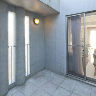 7階(自邸)中庭/大通り側のコンクリート壁は細長く開口し、騒音などを適度に遮りつつ光と風をとり込む造りに。窓越しのリビングは写真奥の窓で屋上庭園とも面しており、両サイドからたっぷりと日差しが入る