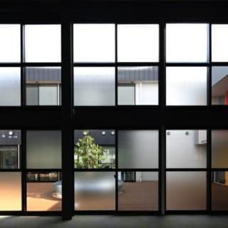 撮影:GEN INOUE  窓~中庭面/中庭に向かった窓を工場内部から望んだ写真。半分がすりガラスのサッシを用い、市松模様を表現。魅力的なデザインに仕上がっている。また、圧迫感がなく、適度に視覚を遮る役割もある