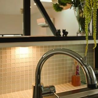 カウンター立ち上がり壁にあしらった透明のガラスタイルが、ステンレスの硬質なテクスチャーに変化をつける。インテリア好きな奥様がセレクト