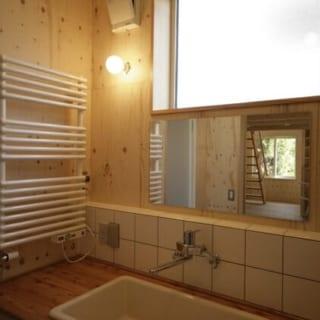 洗面所は天井を高めに設定。開口部を大きく取った高窓で自然光をいっぱいに取り入れている。一部を滑り出し窓にすることで、掃除の際は換気も可能だ。床にはリノリウムを敷設。天然素材ならではの優しい風合いを味わうことができ、比較的メンテナンスもしやすい