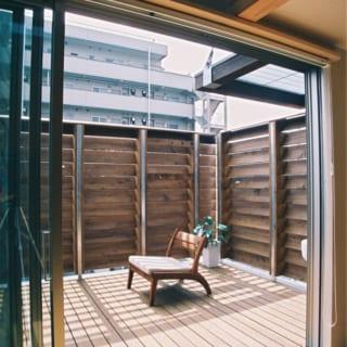 2階 テラス(室内から)/テラス床材とルーバーフェンスは耐久性の高い高熱乾燥木材とベイヒバ。床はリビングとフラットになっていて、ひとつながりのような一体感がある。暖かい時季は窓を開放するとリビングにいながら半戸外のような心地よさを味わえる